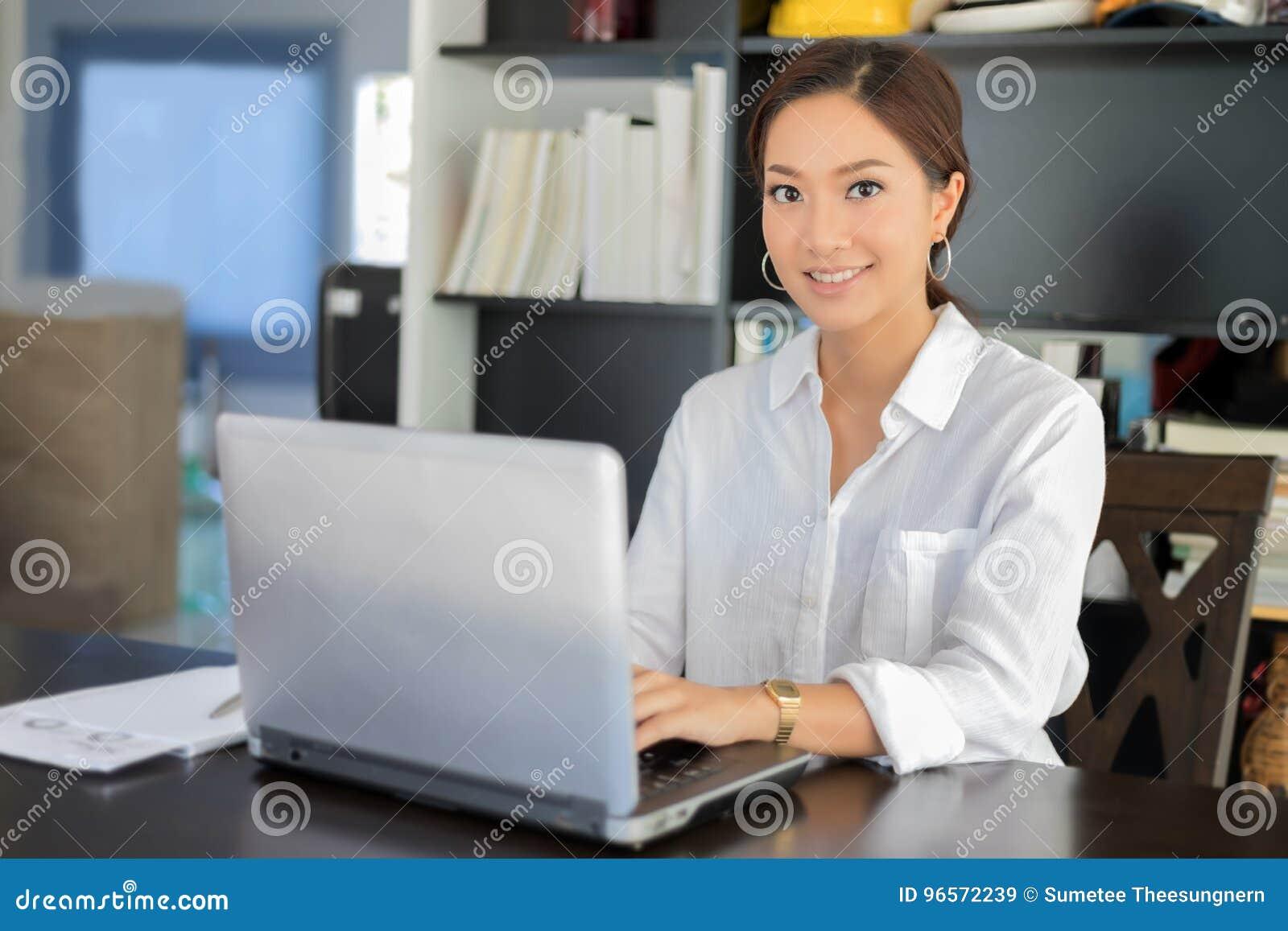 Aziatische bedrijfsvrouwen notitieboekje gebruiken en glimlachen die gelukkig voor worki