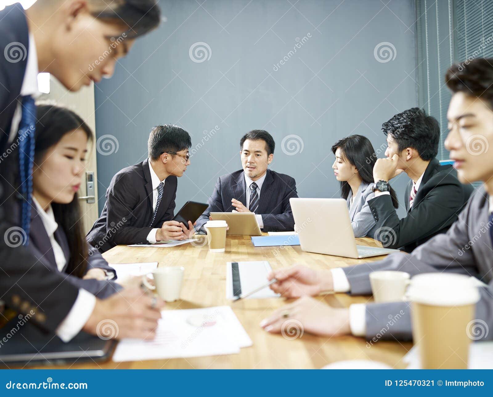Aziatische collectieve mensen die zaken in vergadering bespreken