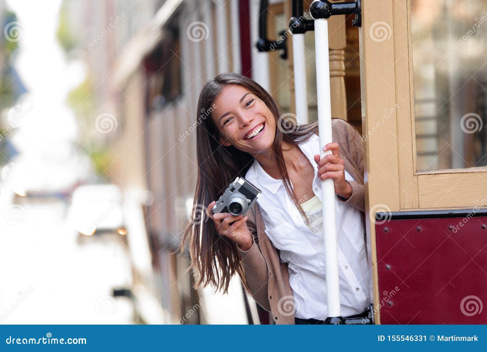 Aziatische de vrouwentoerist die van de reislevensstijl het beroemde systeem van de tramspoorkabelwagen in de stad van San Franci