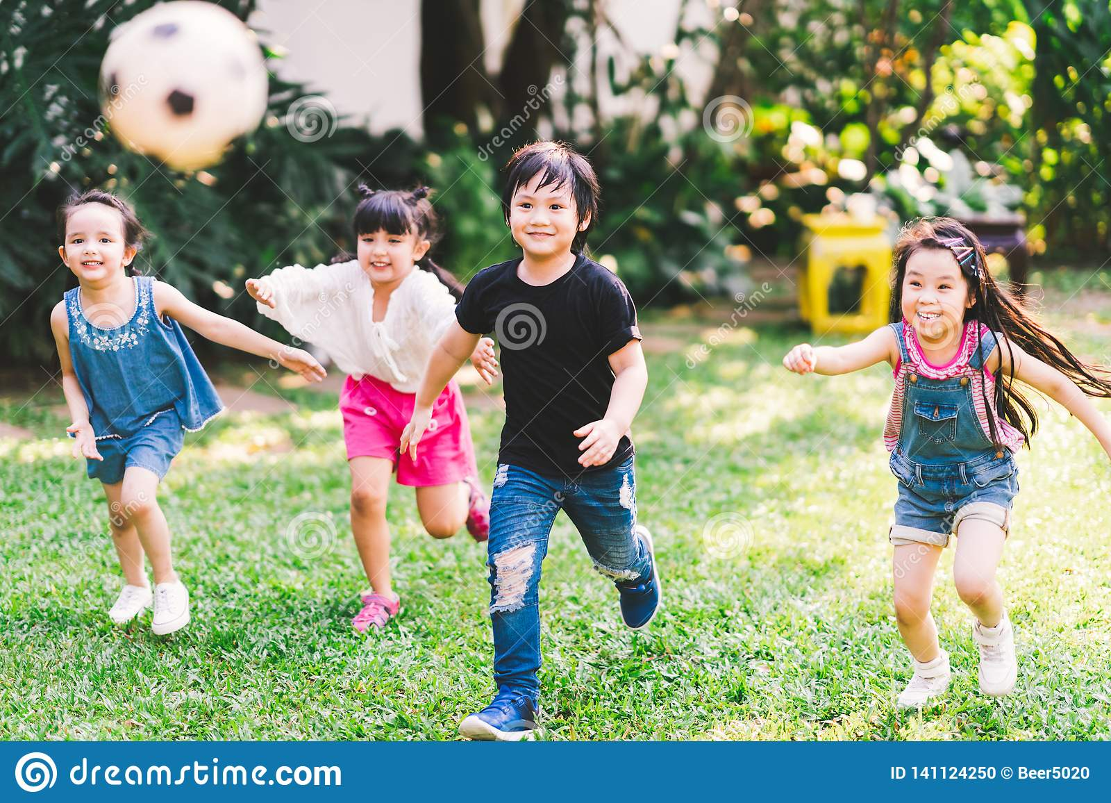 Aziatische en gemengde ras gelukkige jonge jonge geitjes die speelvoetbal samen in tuin in werking stellen De multi-etnische kind