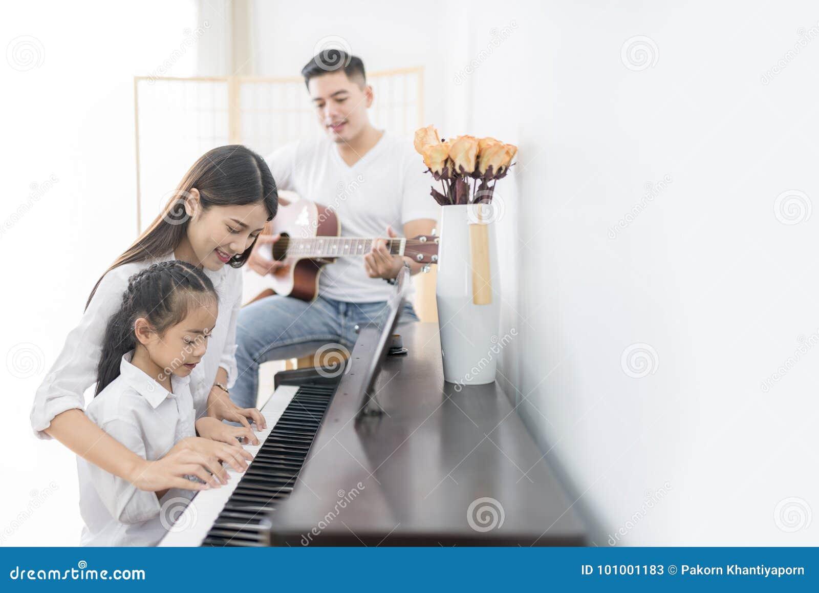 Aziatische familie, moeder en dochter het spelen Piano, vader het spelen
