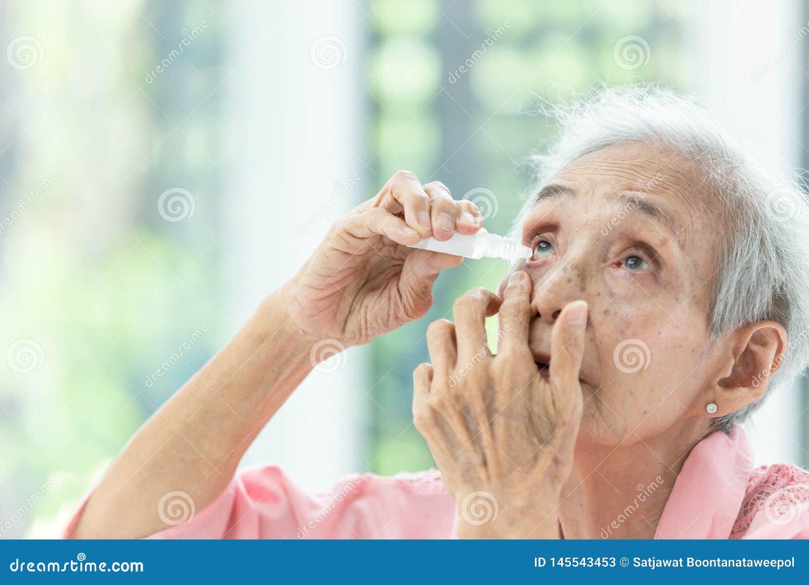 Aziatische hogere vrouw die oogdaling, close-upmening zetten van bejaarde persoon die fles eyedrops in haar ogen met behulp van,