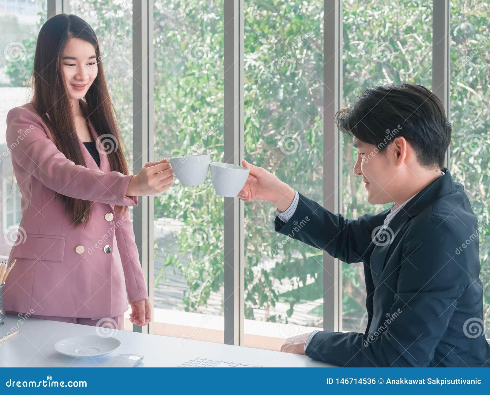 Aziatische jonge knappe zakenman en mooie bedrijfsvrouwengroeten door koffie