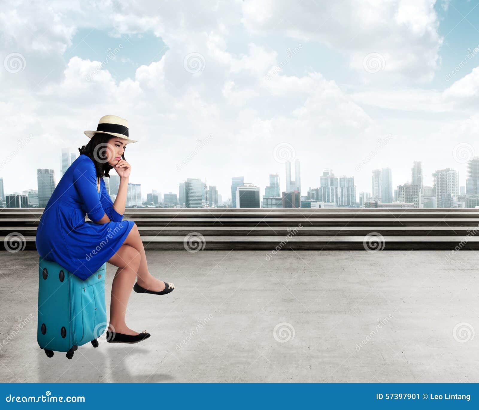 Aziatische jonge vrouwenreiziger met droevig gezicht, die op de koffer zitten