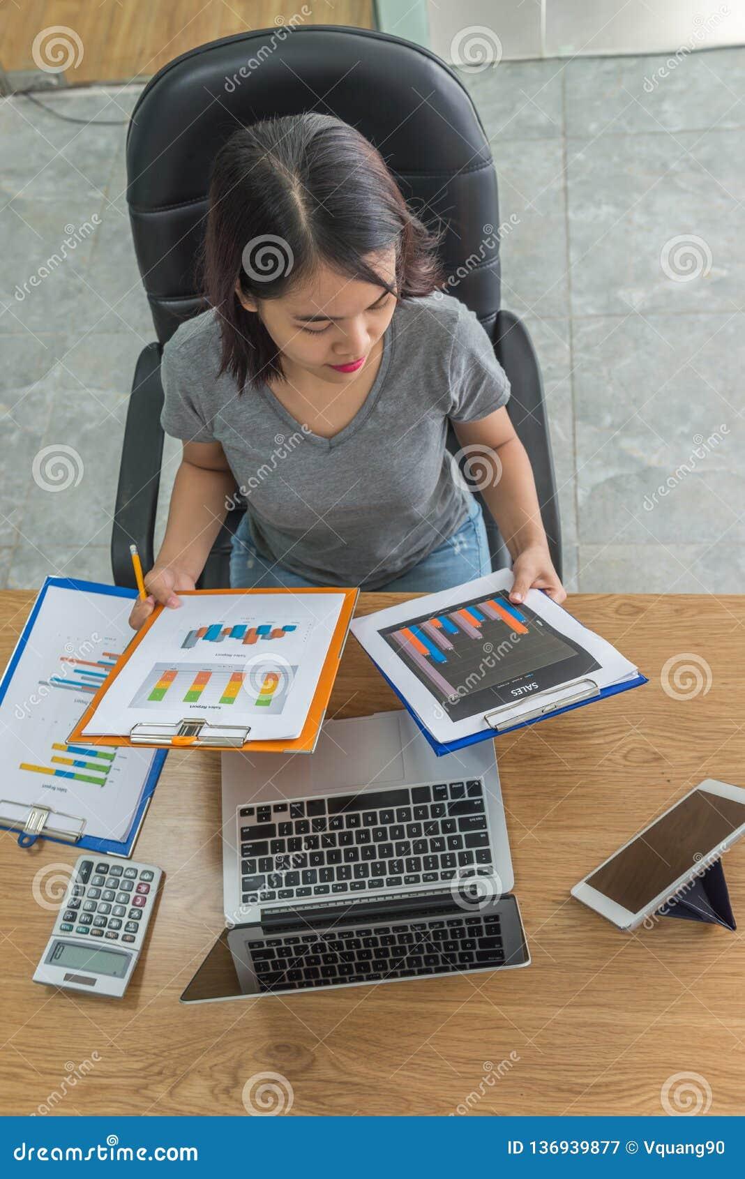 Aziatische manager die verkooprapporten in haar bedrijfsbureau controleren