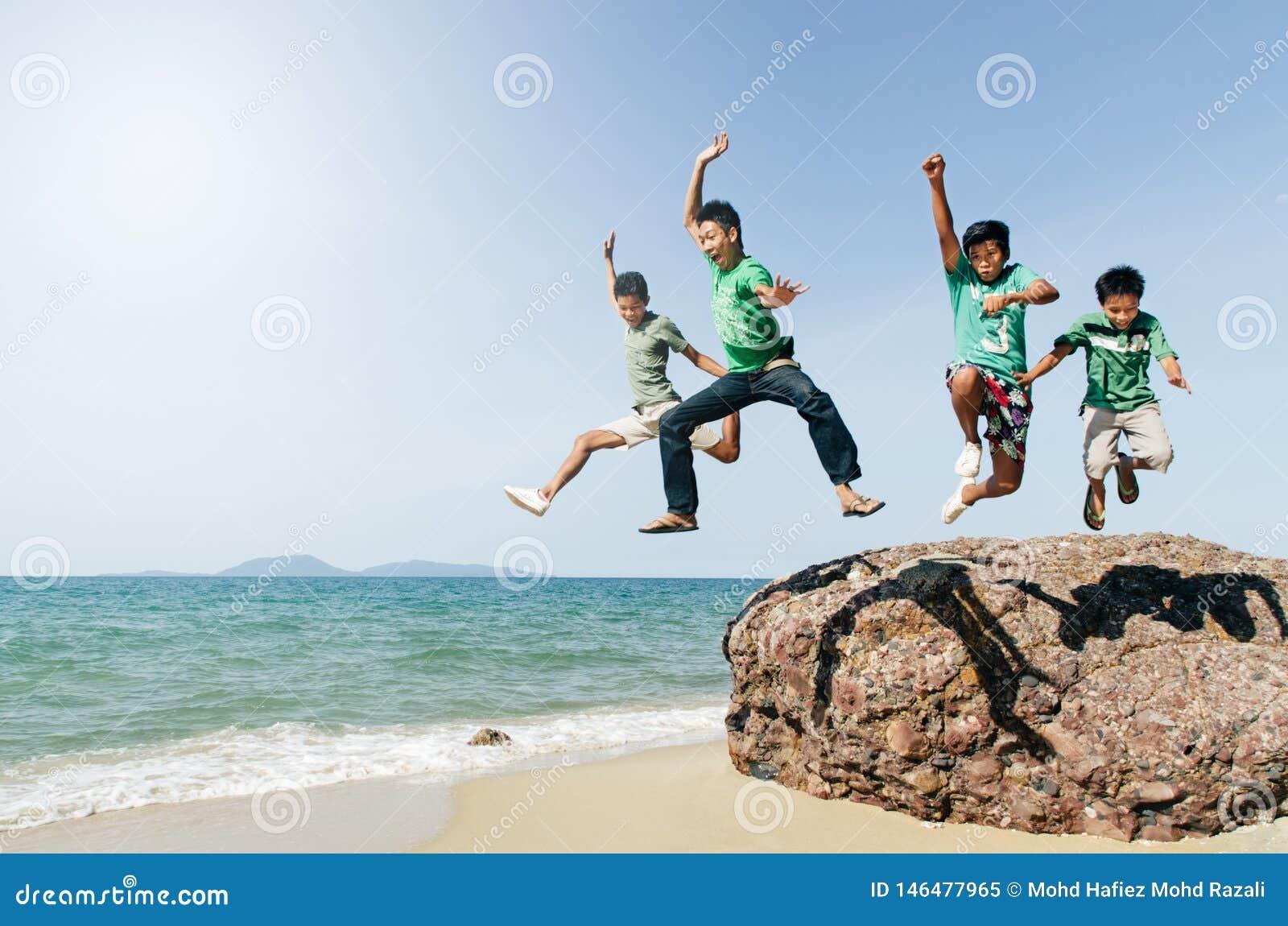 Aziatische mannelijke tiener vier die en pret springen hebben bij het strand