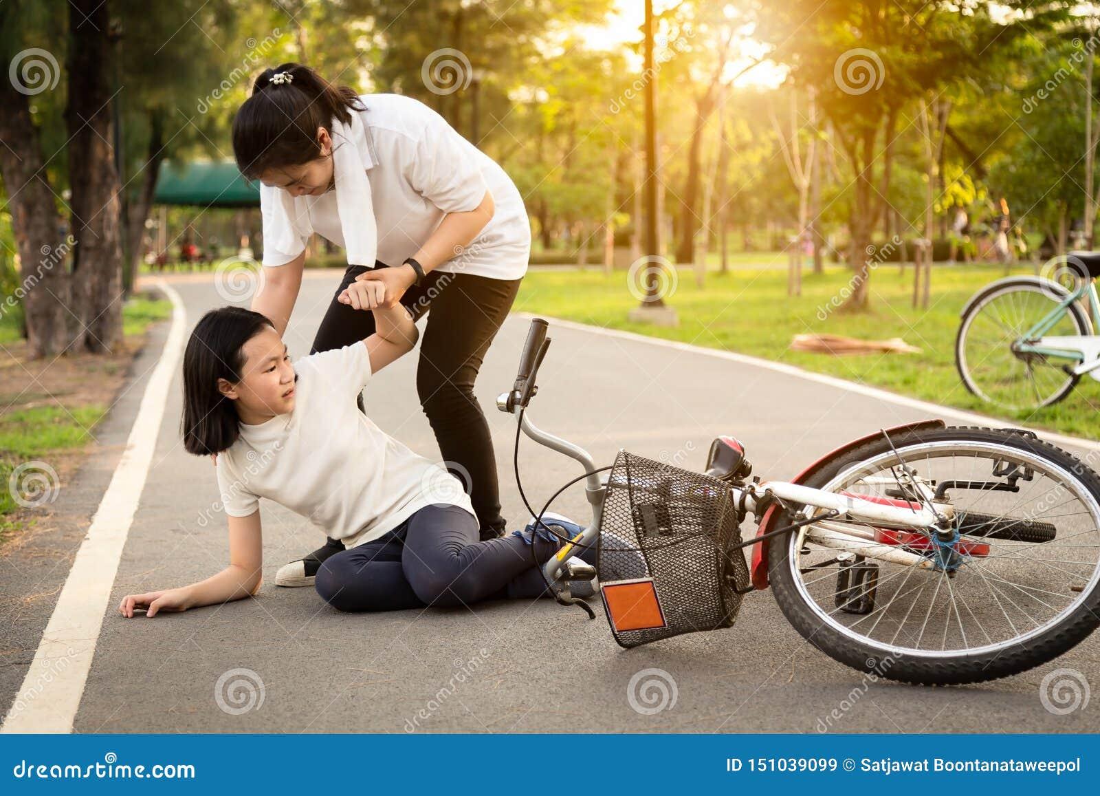 Aziatische meisjezitting neer op de weg met een beenpijn toe te schrijven aan een fietsongeval, de fietsdaling dichtbij het vrouw