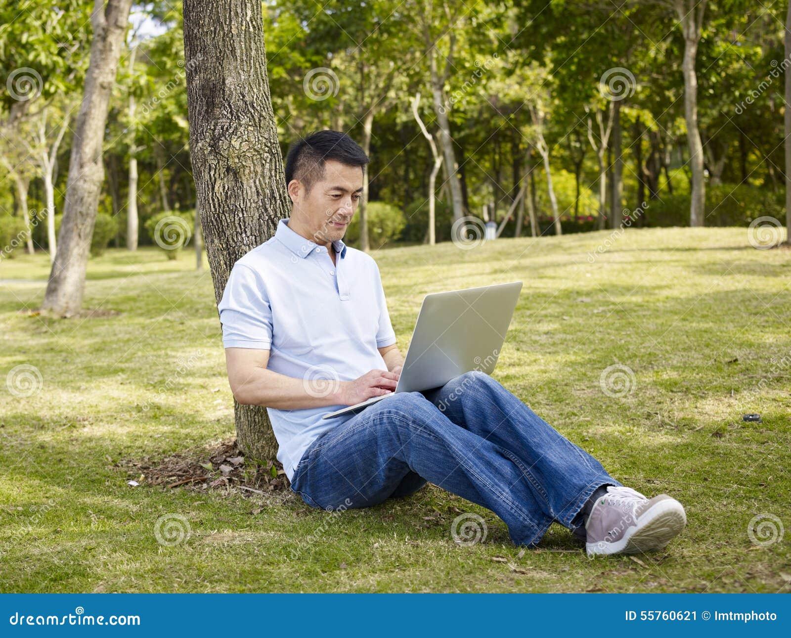 Aziatische mens die laptop in openlucht met behulp van