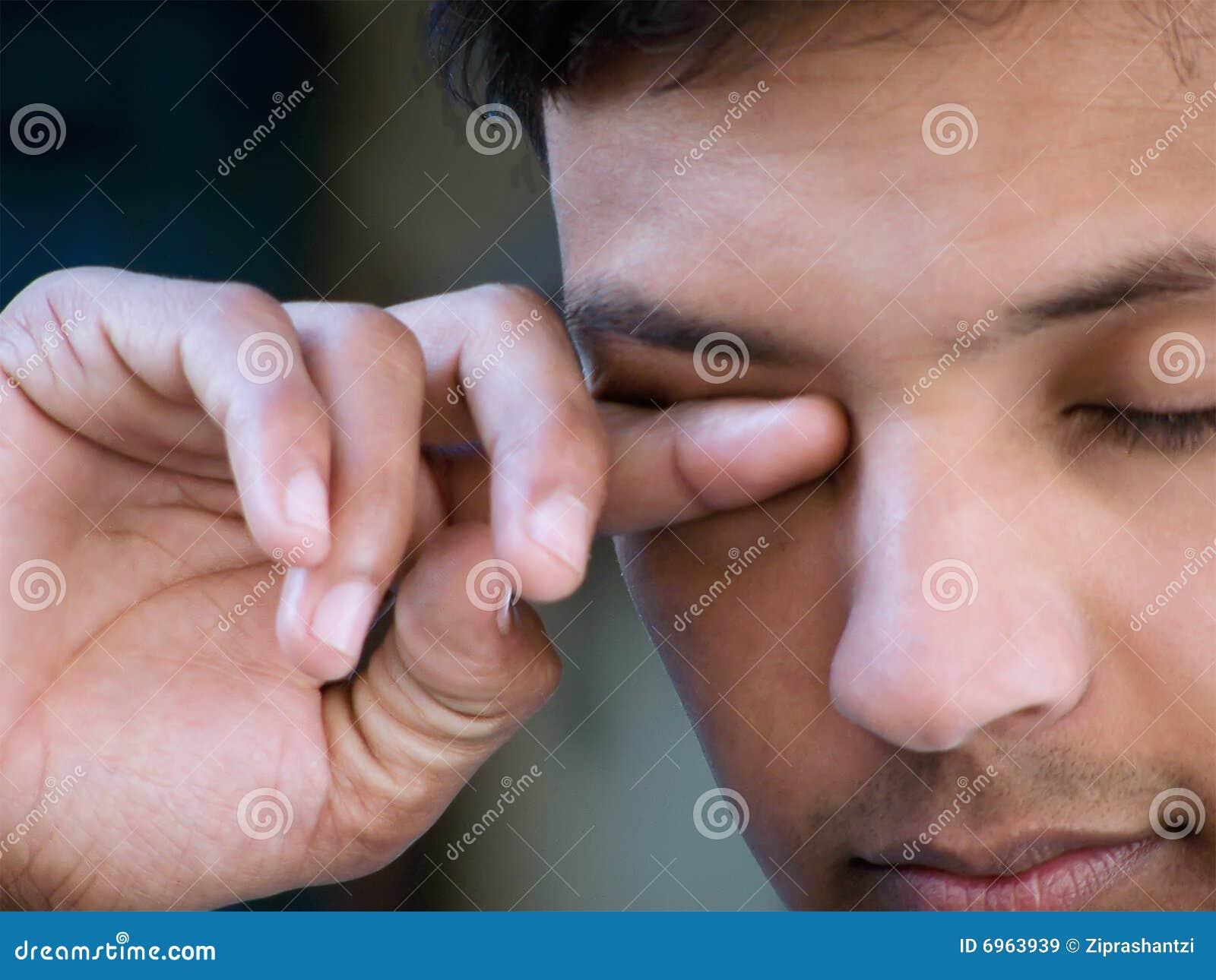 Aziatische mens die ogen wrijft