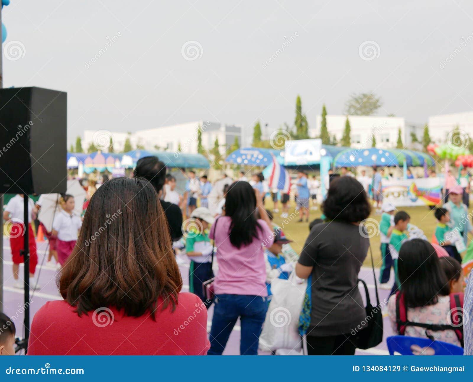 Aziatische moeder die op haar kinderen letten deelnemend aan een gebeurtenis van de sportdag op school