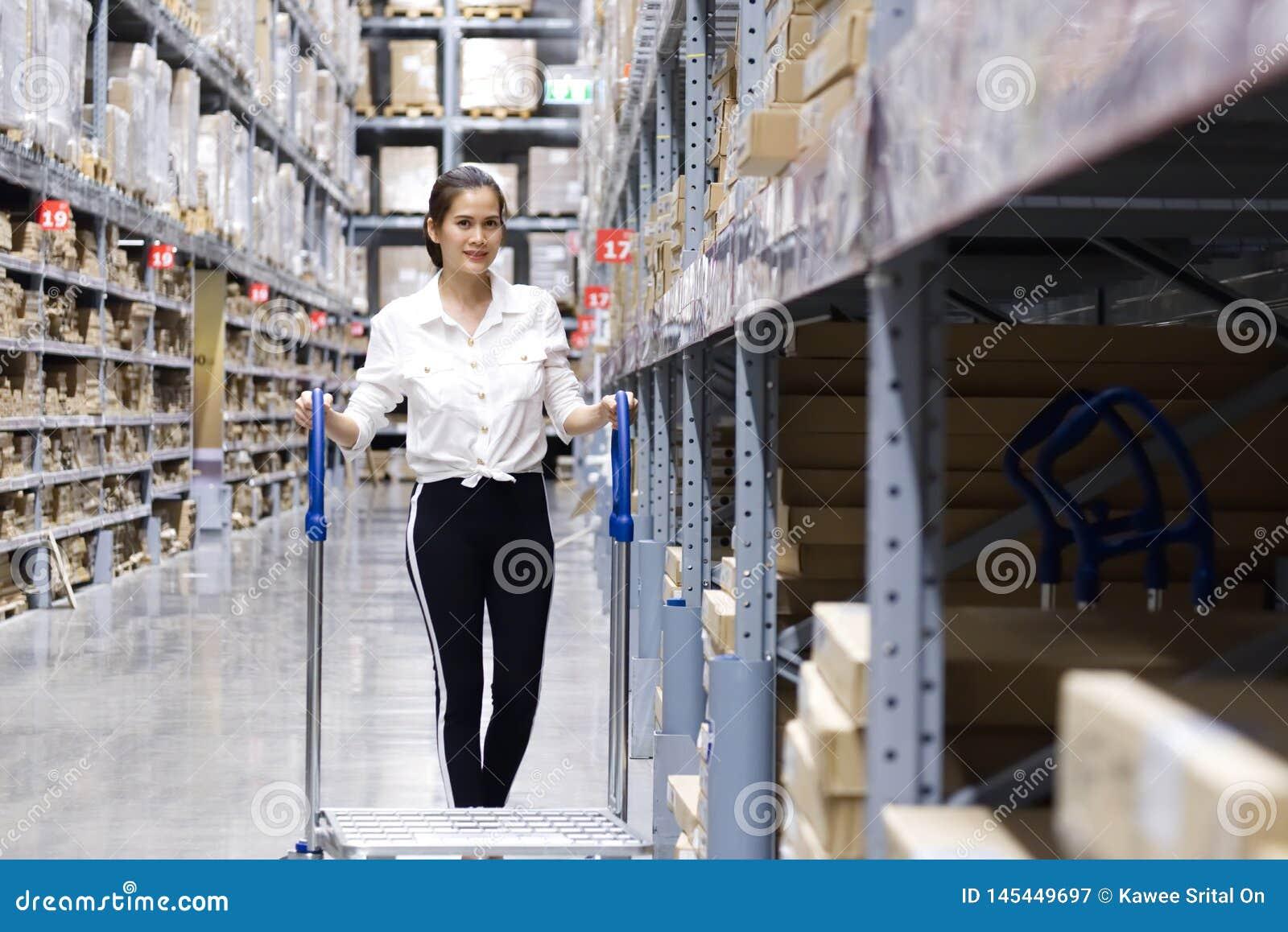 Aziatische mooie klant die producten zoeken in opslagpakhuis Het meisje die de kar duwen en vindt de goederen om het in de kar te