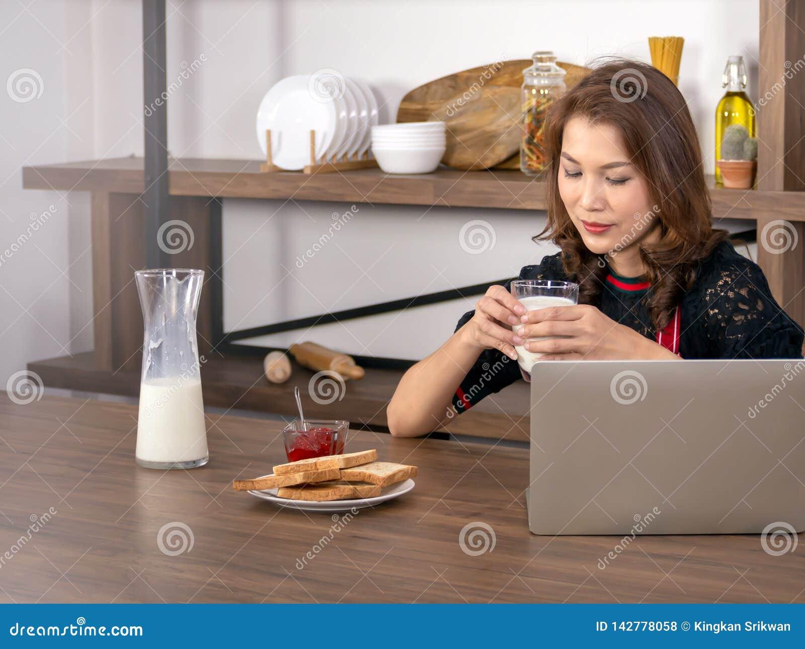 Aziatische mooie vrouw die een glas melk houden die laptop met behulp van