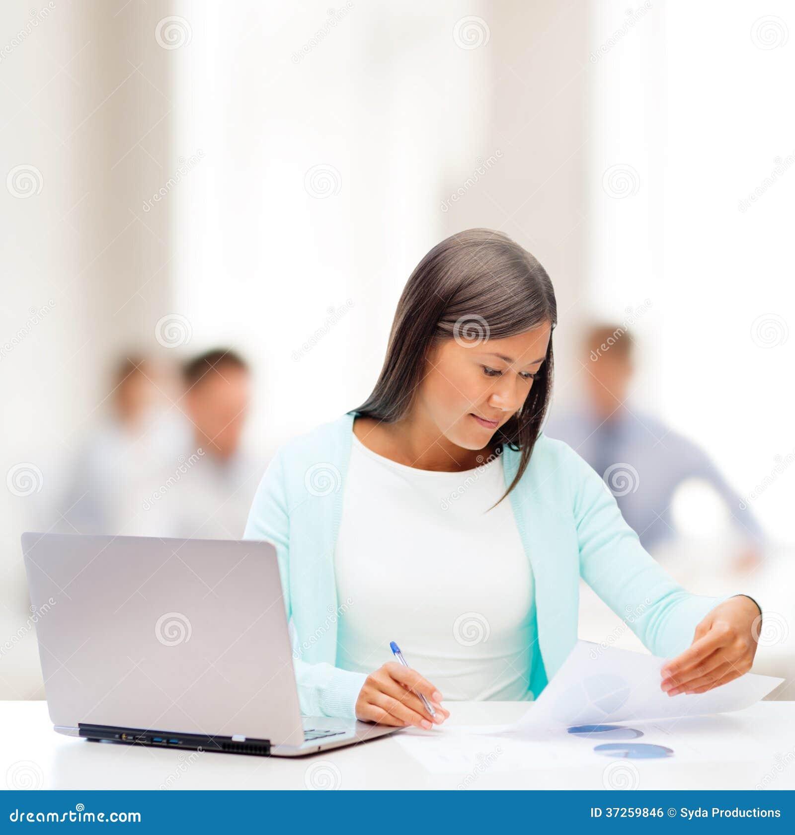 Aziatische onderneemster met laptop en documenten