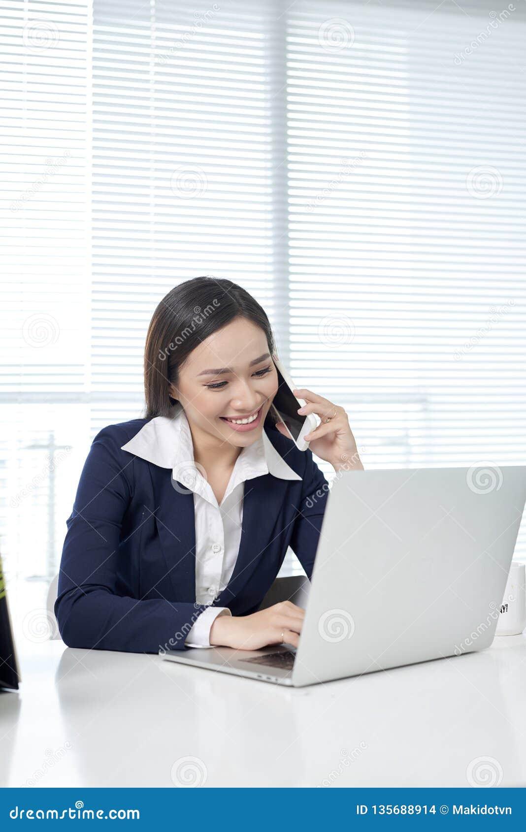 Aziatische onderneemsterzitting door bureau met laptop en gebruiken mobiel in bureau