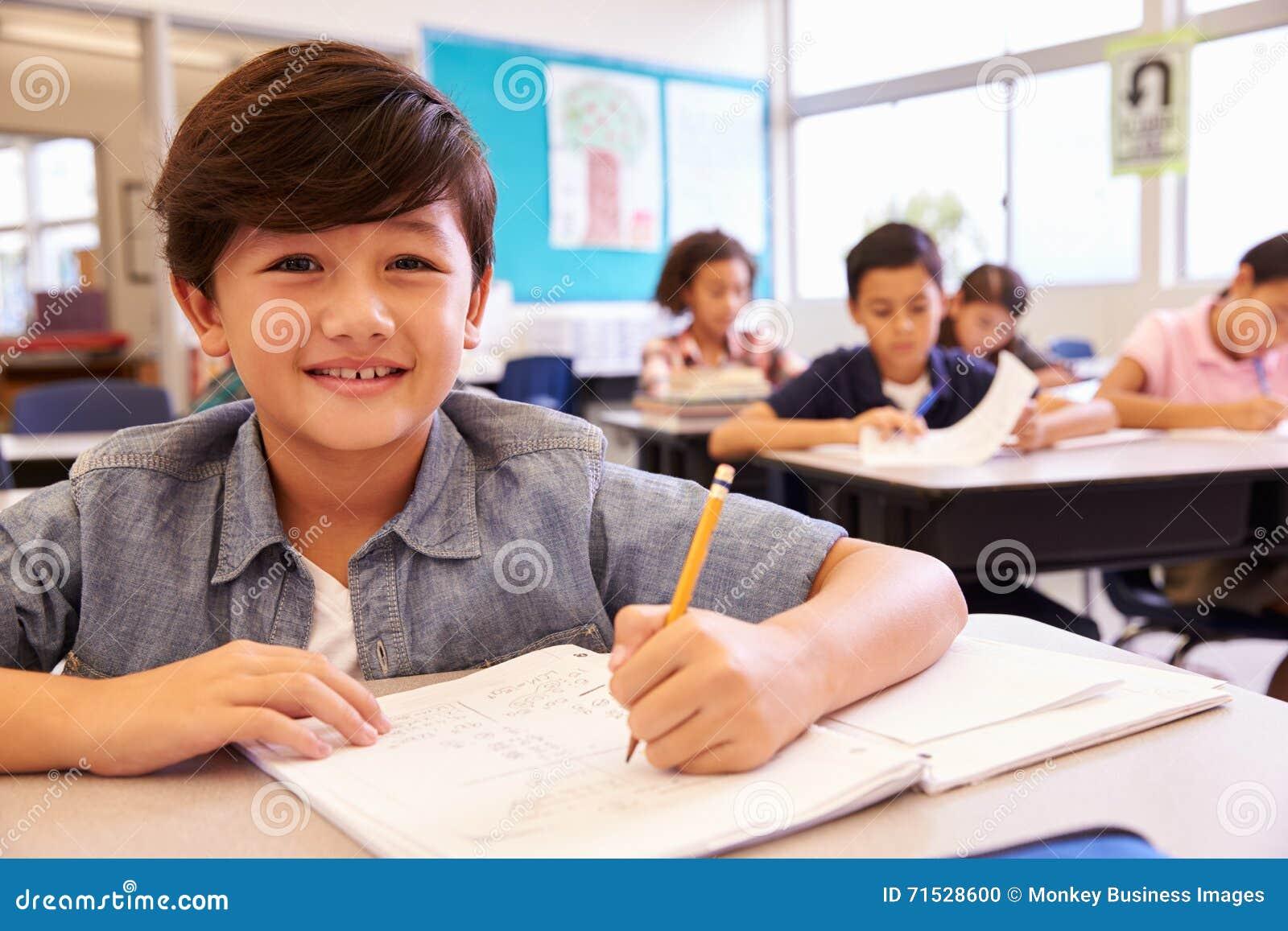 Aziatische schooljongen die in basisschoolklasse aan camera kijken