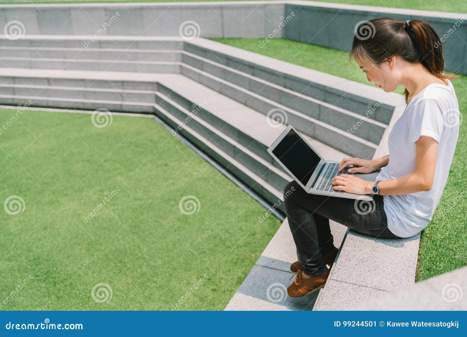 Aziatische student of freelance vrouw die laptop op trede in universitaire campus of openbaar park met behulp van Informatietechn