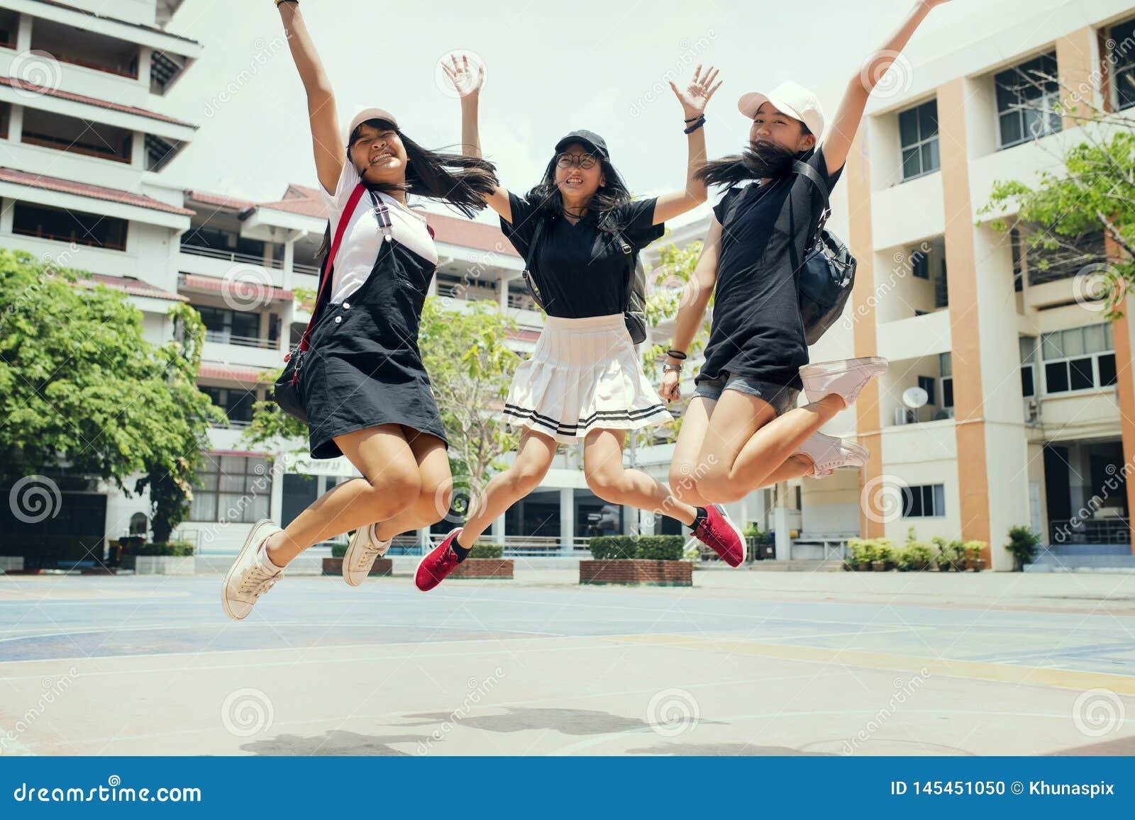 Aziatische tiener drie die medio lucht met gelukemotie springen tegen de schoolbouw achtergrond
