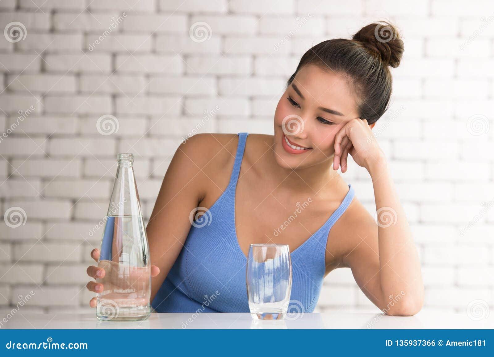 Aziatische vrouw in blije houdingen met fles en glas drinkwater aan de kant