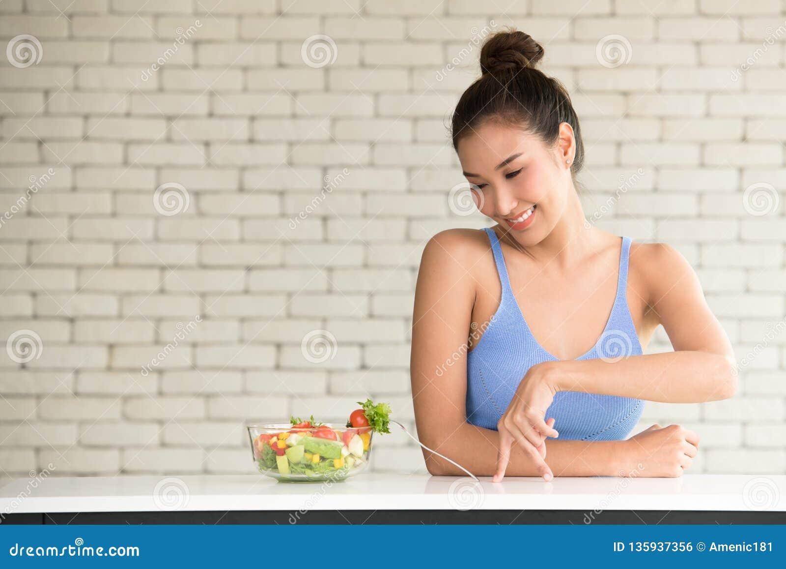 Aziatische vrouw in blije houdingen met saladekom aan de kant