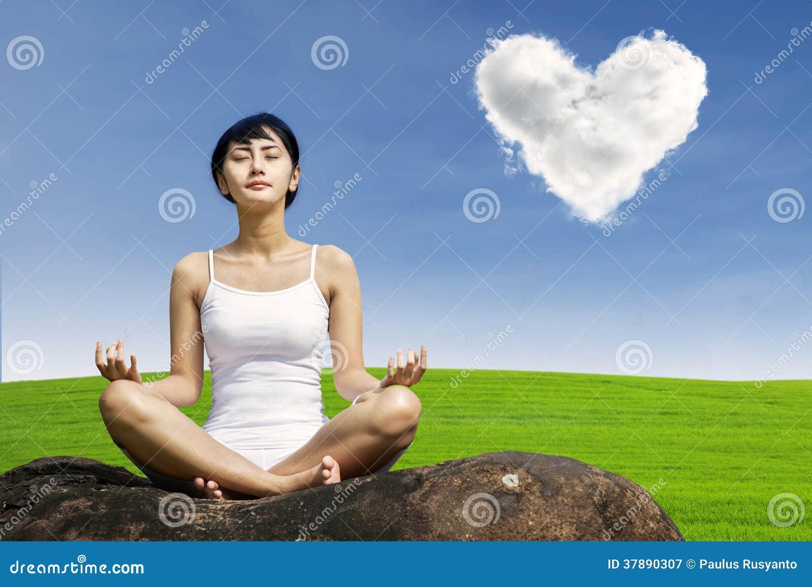 Aziatische vrouw die bij groen gebied mediteren