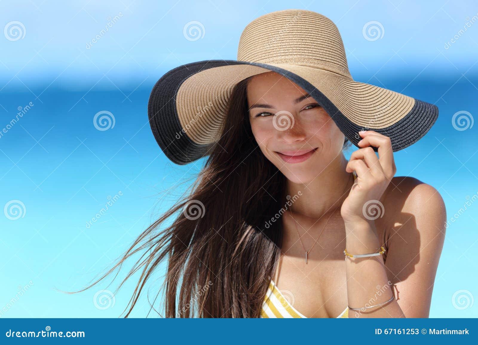 Aziatische vrouw met strandhoed voor de bescherming van de gezichtszon