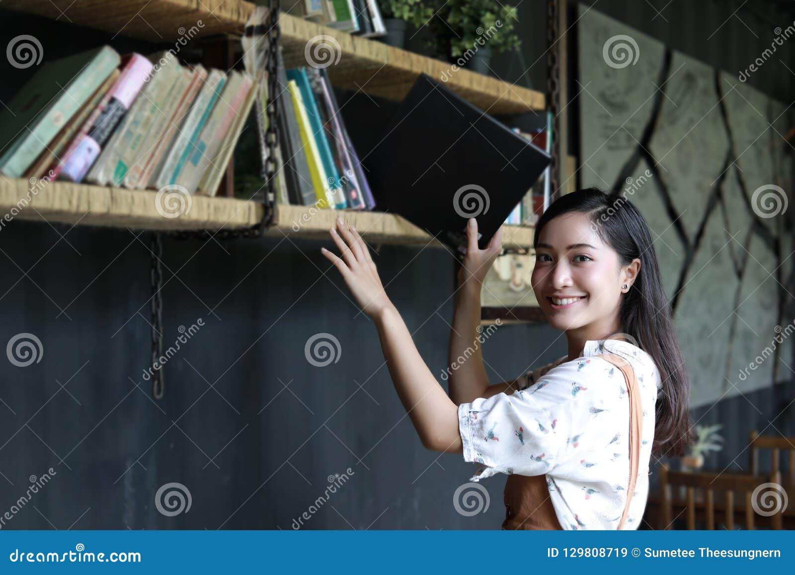 Aziatische vrouwelijke studenten die voor sectie over boekenplank houden