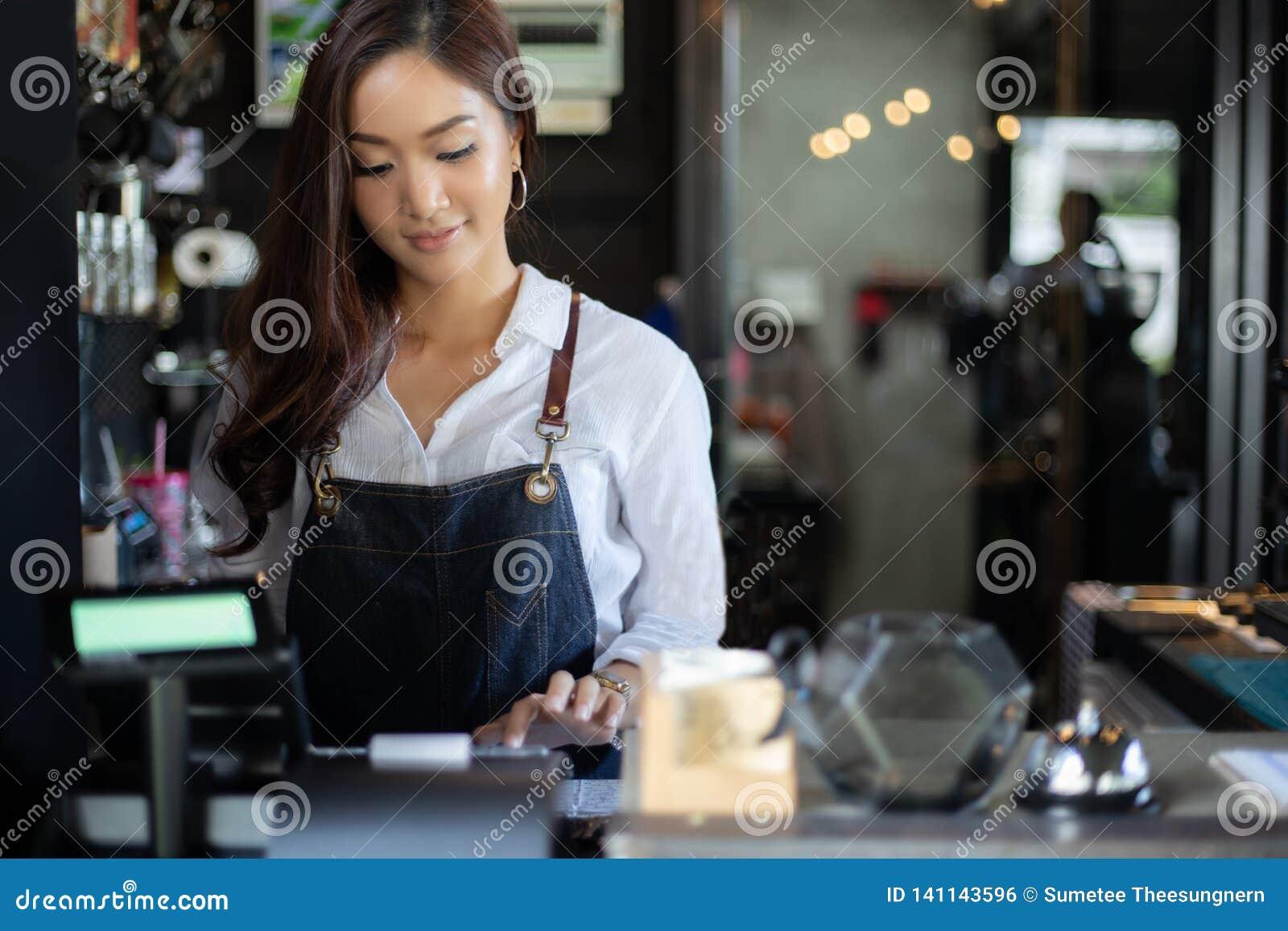 Aziatische vrouwen Barista die en koffiemachine in de teller van de koffiewinkel glimlachen met behulp van - Werkende vrouwen kle