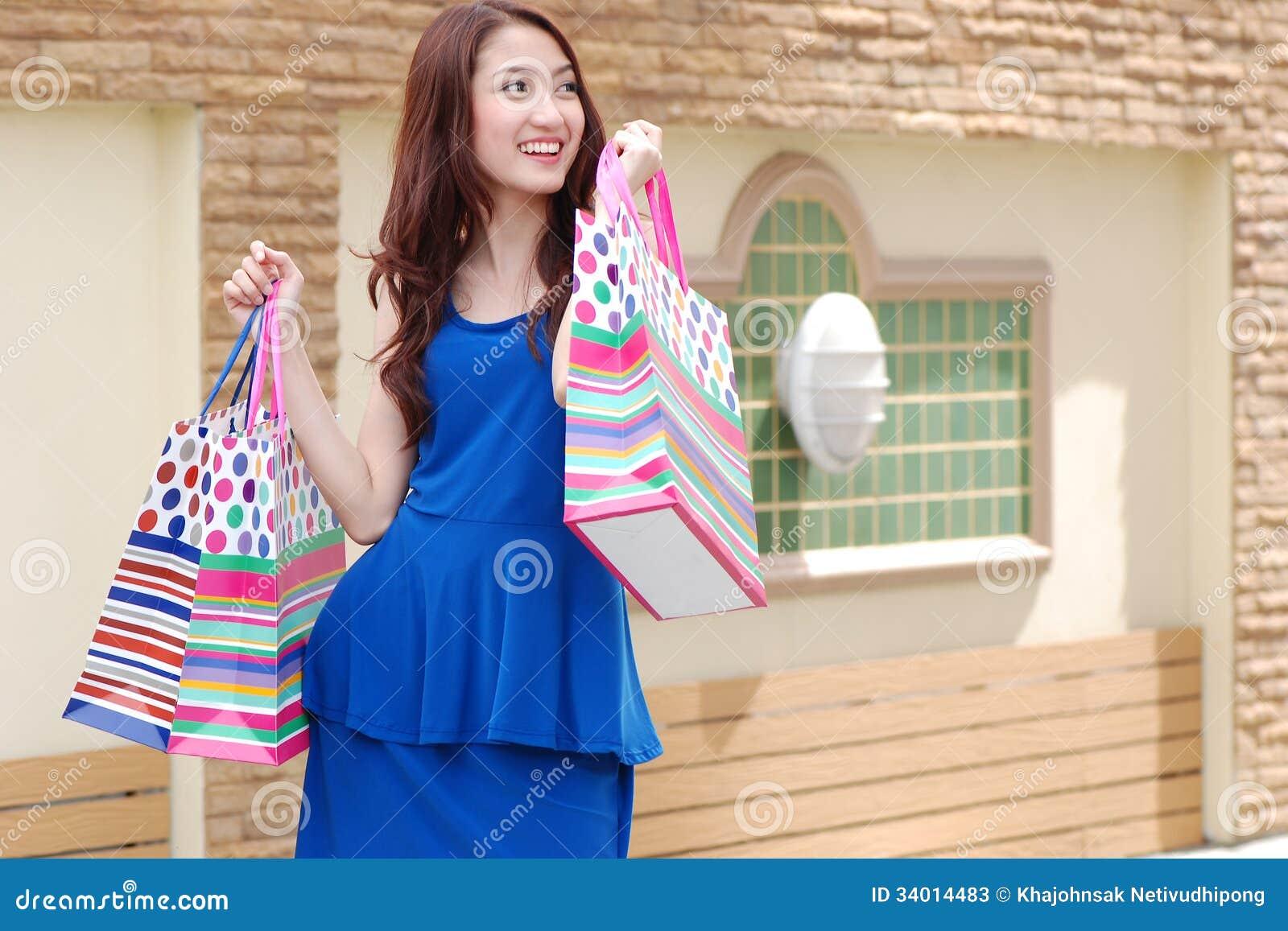 Aziatische vrouwen bij het houden van heel wat het winkelen zak in Supermarkt