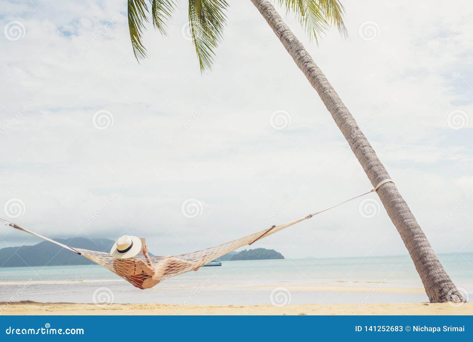 Aziatische vrouwen die in de vakantie van de hangmatzomer op strand ontspannen