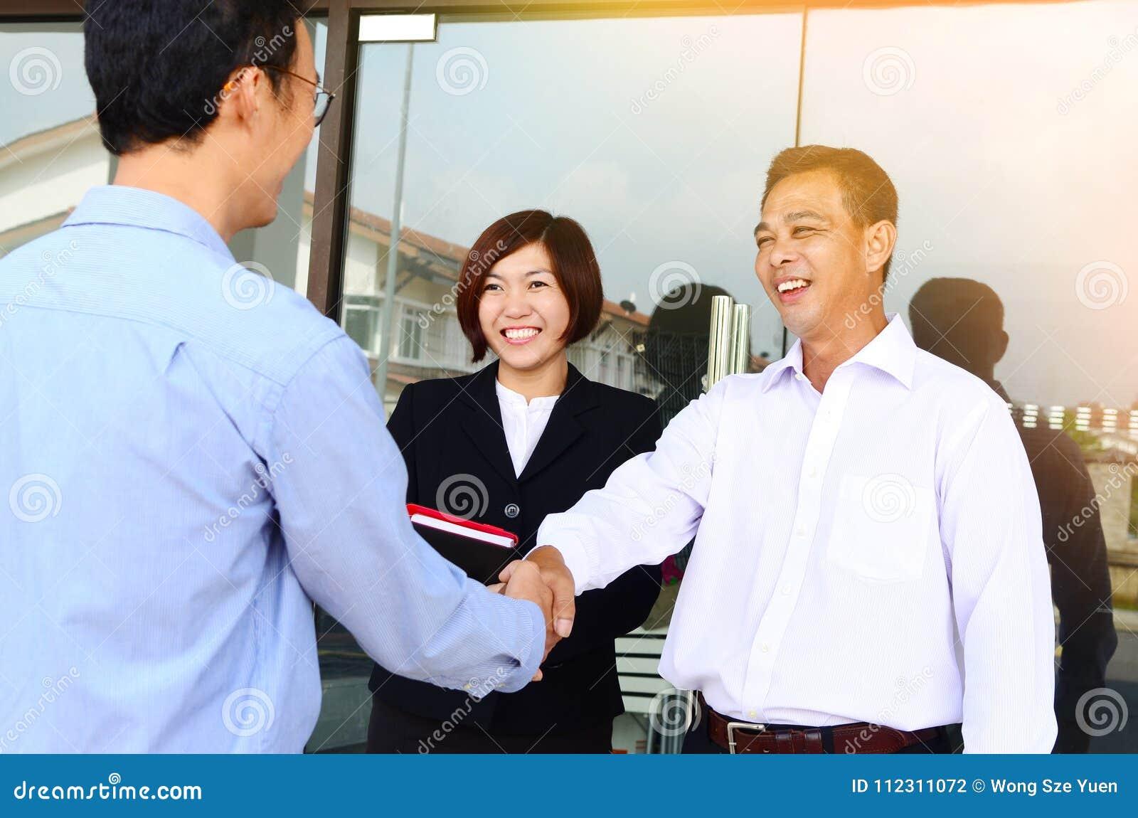 Aziatische zakenlieden die handen schudden