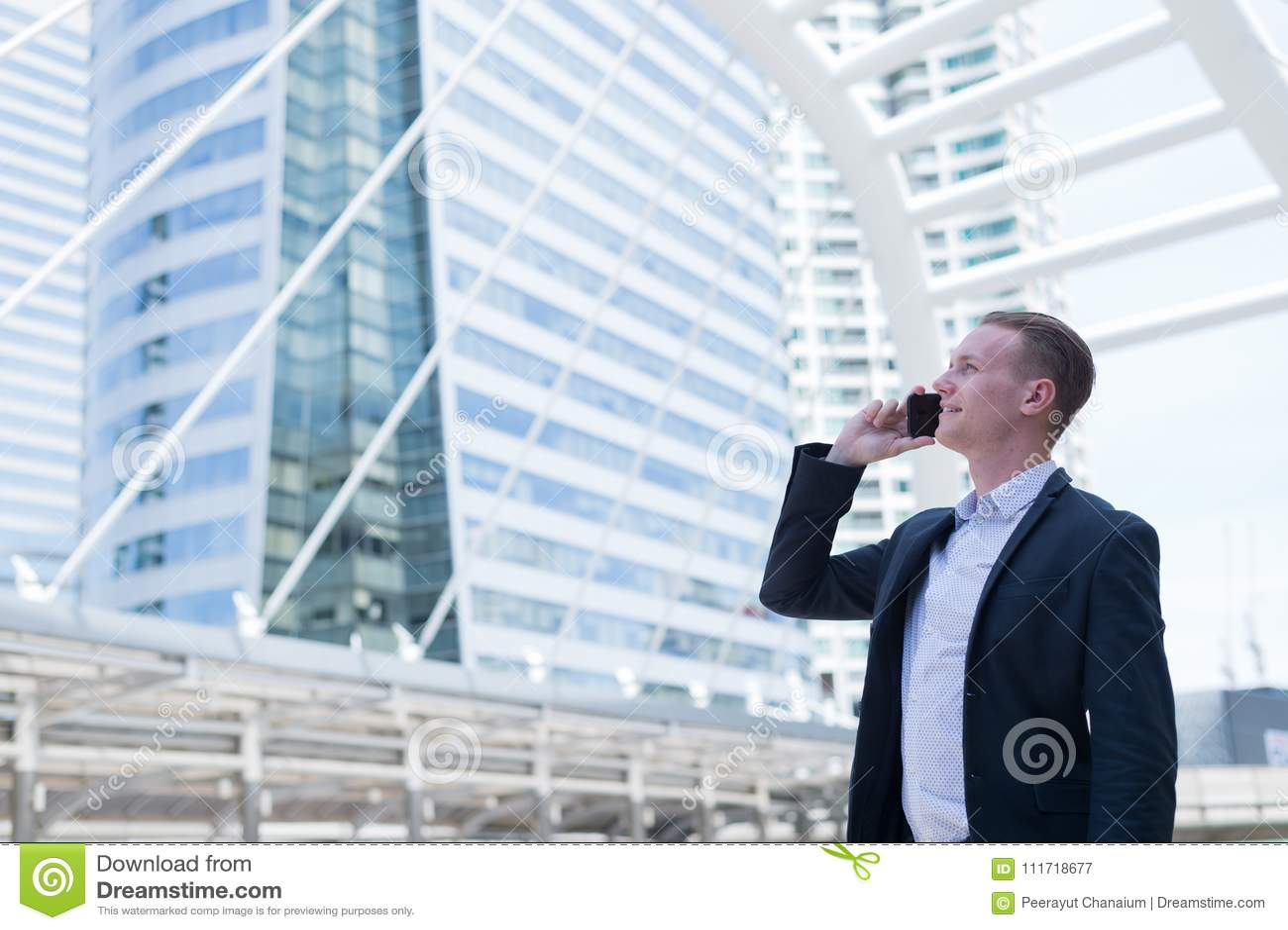 Aziatische zakenmanglimlach en het gebruiken van celtelefoon om over bedrijfssucces en financiële toekomst, met exemplaarruimte t