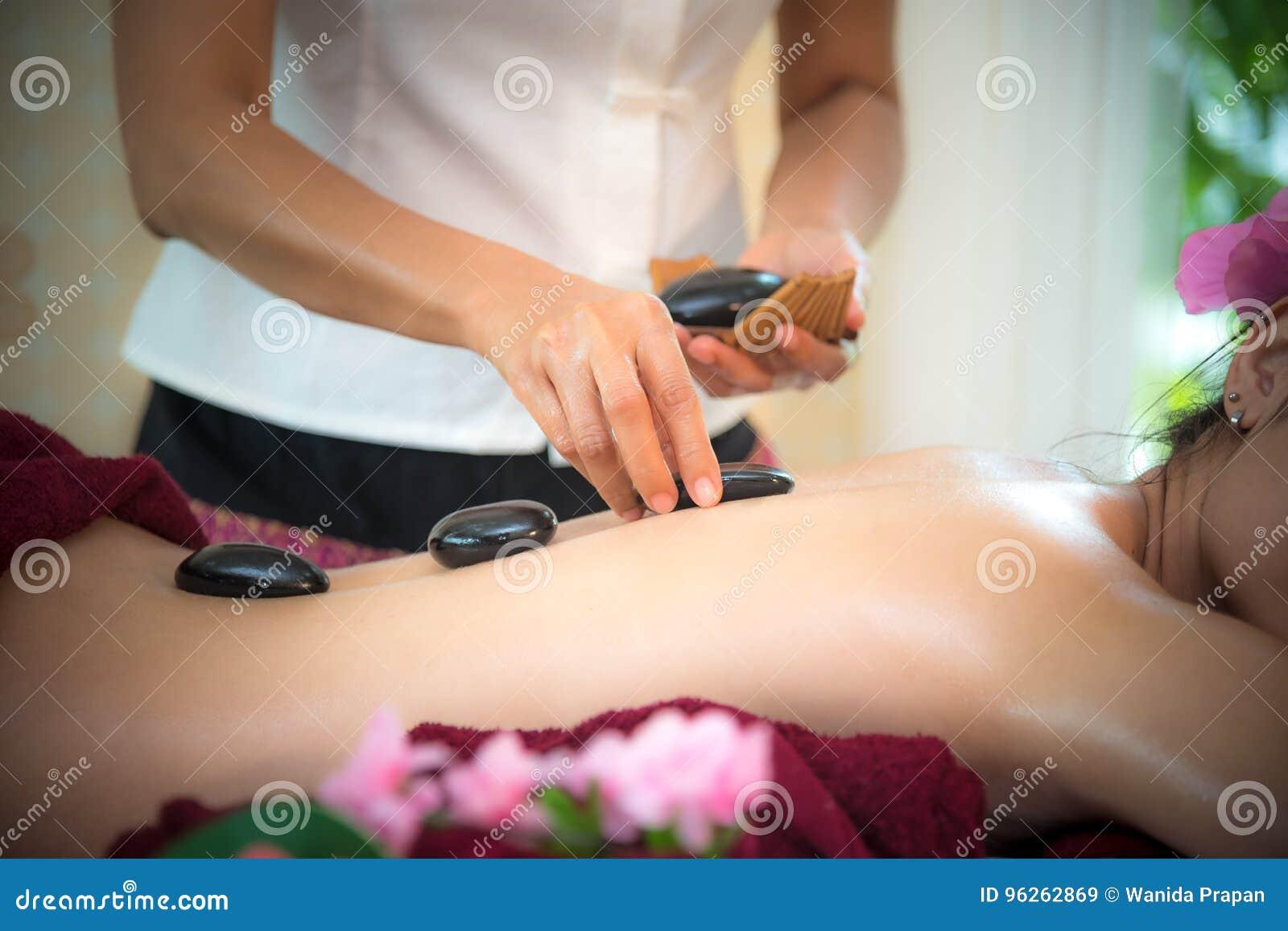 Azja piękna kobiety łgarski puszek na masażu łóżku z tradycyjnymi gorącymi kamieniami wzdłuż kręgosłupa przy Tajlandzkim zdrojem