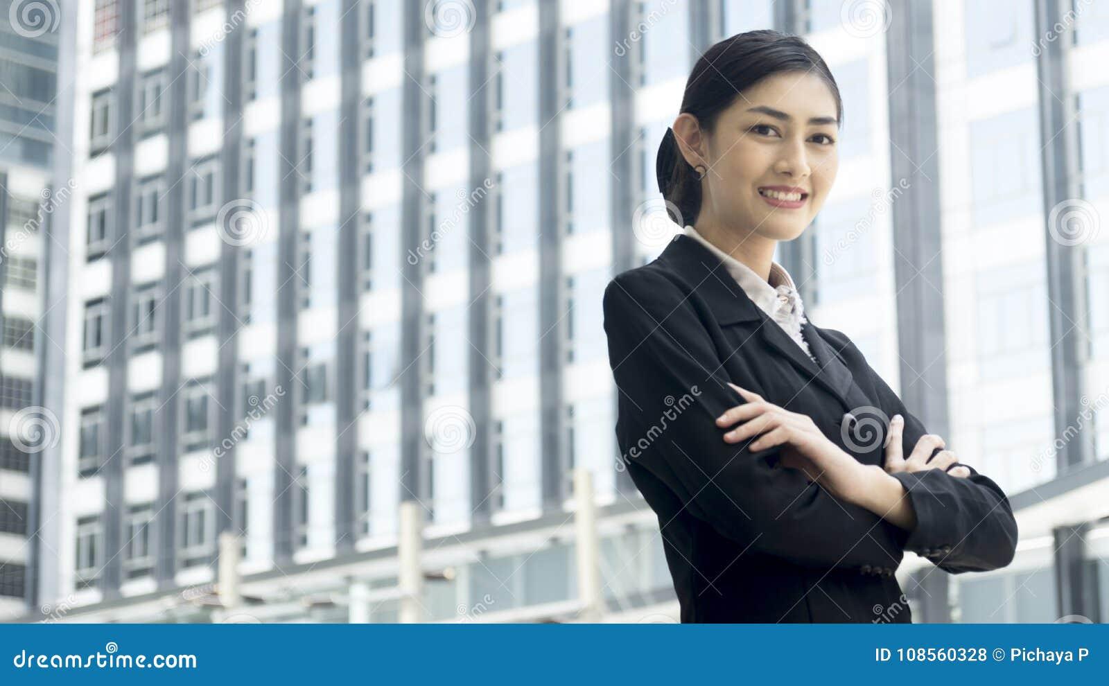 Azjatyccy biznesowej kobiety stojaki z ufnym przeniesieniem przy plenerowym pu