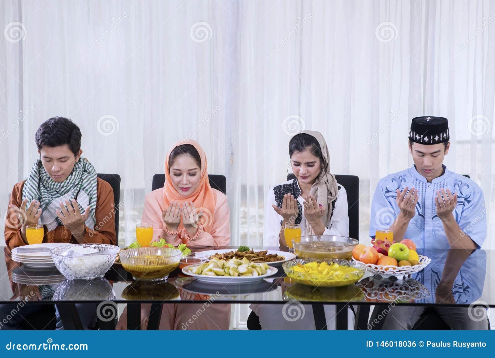 Azjatyccy ludzie modlą się wpólnie przed przerwą post