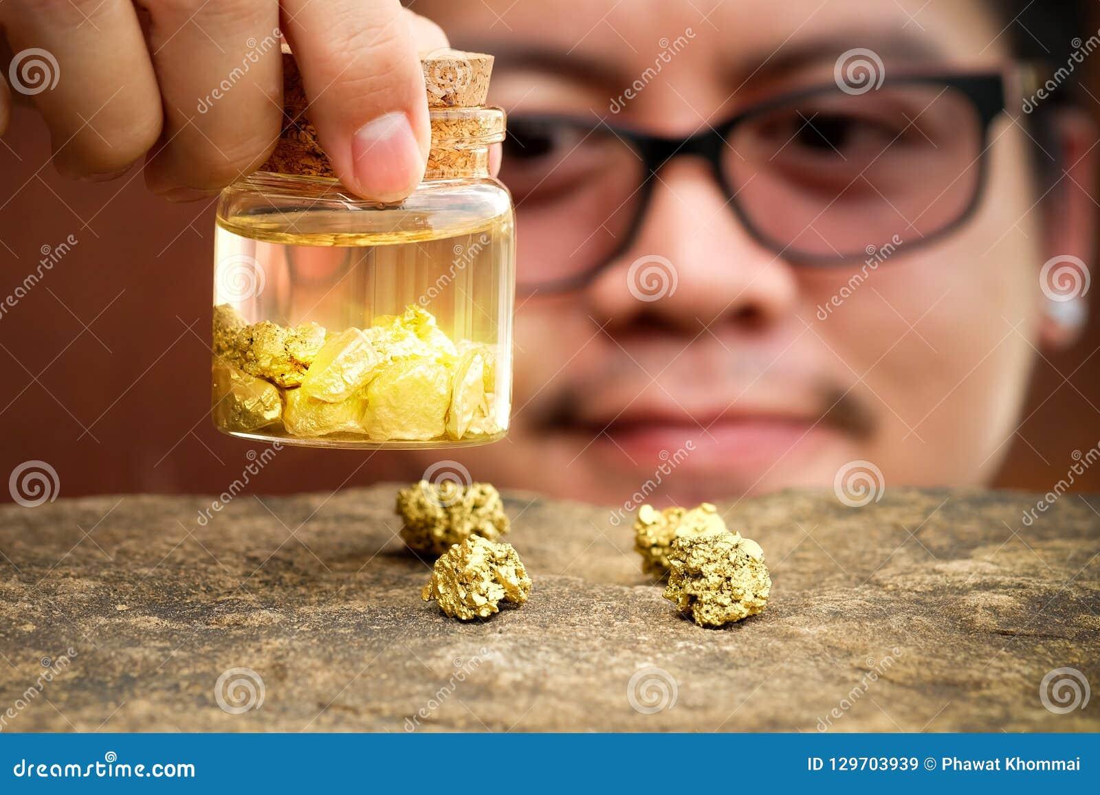 Azjatyccy mężczyźni uśmiechnięci i patrzeją złoto w butelce