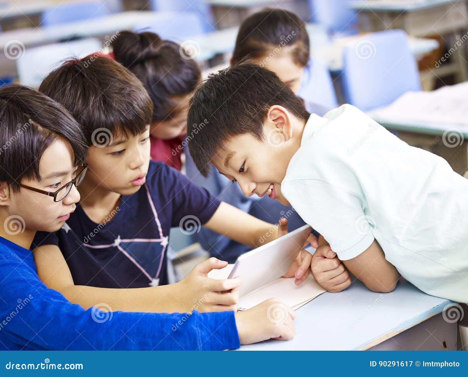 Azjatyccy ucznie używa cyfrową pastylkę wpólnie
