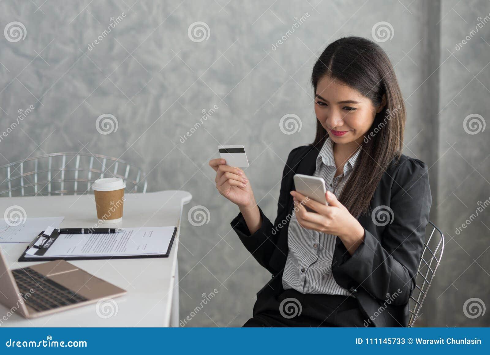 Azjatycka biznesowa dziewczyna w jej staci roboczej kupuje online z cred