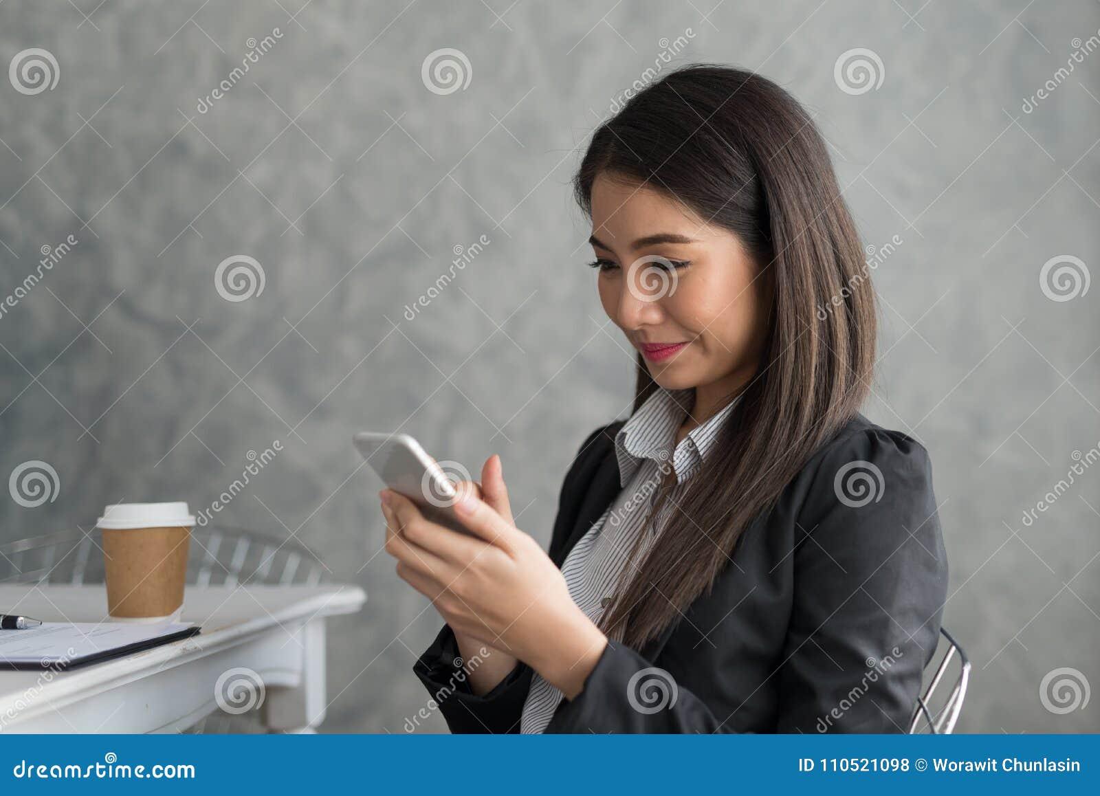 Azjatycka biznesowa dziewczyna w jej staci roboczej przy trzymać filiżankę i