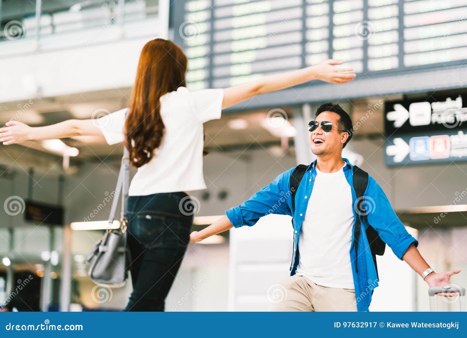 Azjatycka dziewczyna podnosi up jej chłopaka przy lotniskową ` s przyjazdową bramą, powitania z powrotem stwarza ognisko domowe o