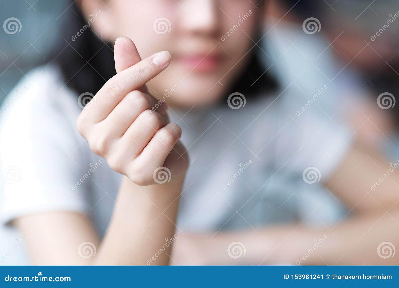 Azjatycka dziewczyna robi Koreańskiemu symbolowi wręczać serce