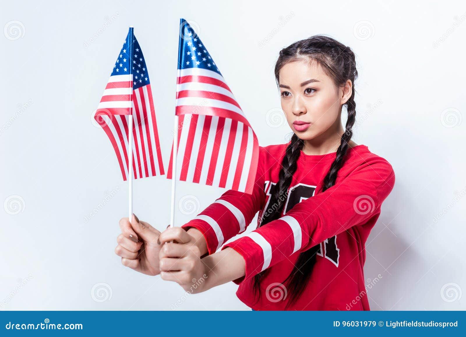 Azjatycka dziewczyna w patriotycznych stroju mienia flaga amerykańskich i patrzeć daleko od