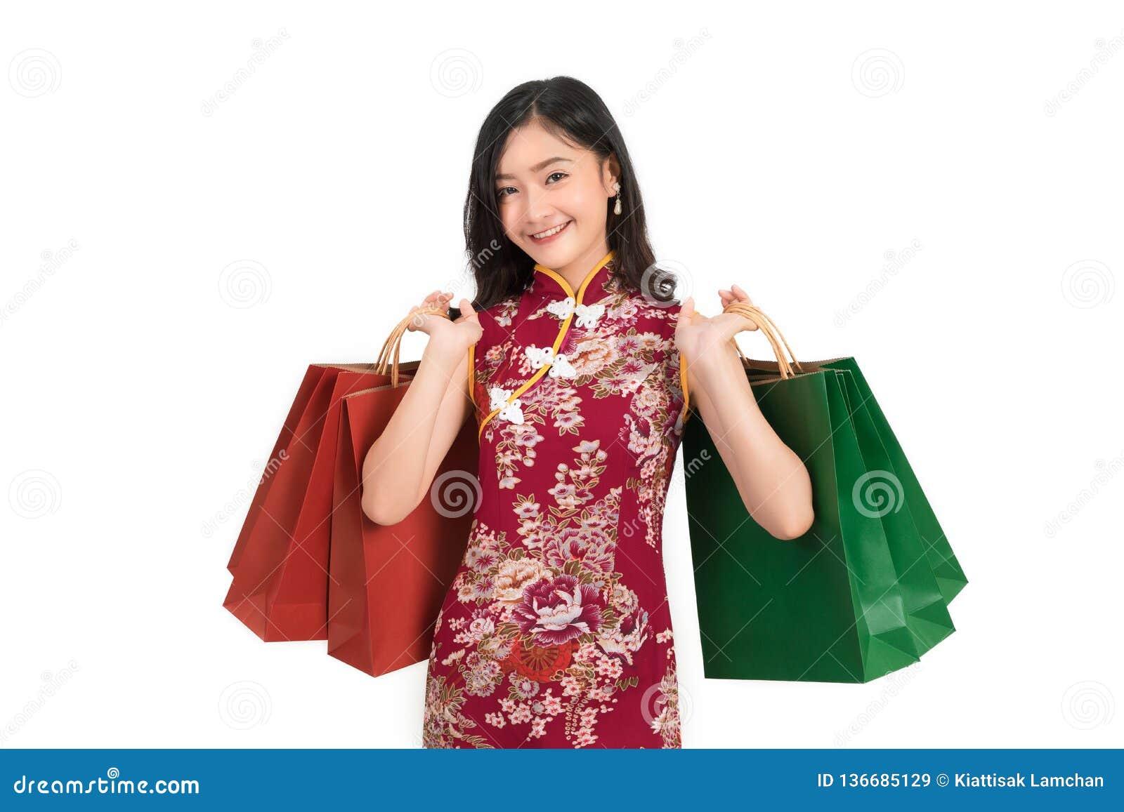 Azjatycka kobieta jest ubranym chińczyk sukni chwyta torby na zakupy cheongsam, qipao uśmiech w chińskim nowym roku