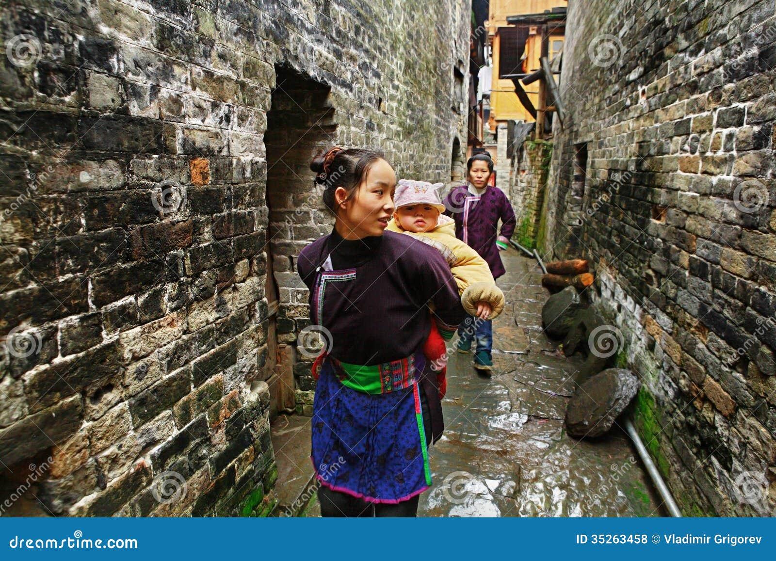 Azjatycka kobieta niesie dziecka za plecy w wiejskim Chiny.