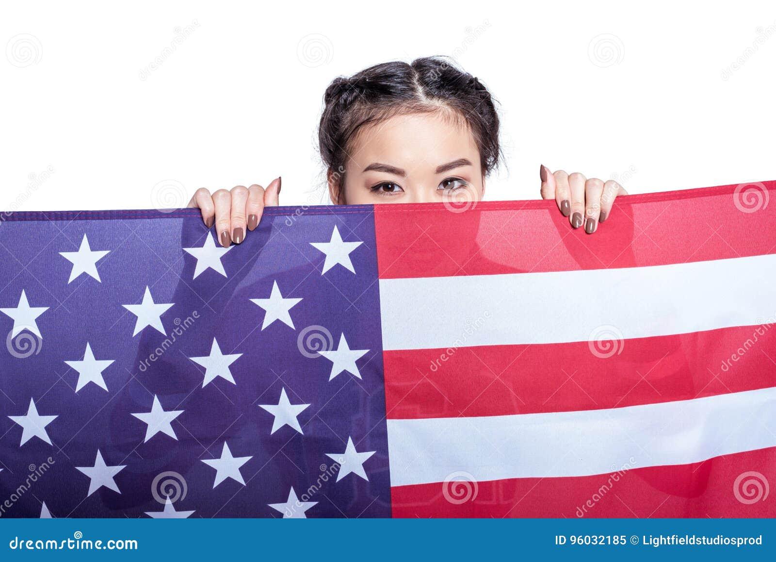Azjatycka kobieta pozuje z flaga amerykańską odizolowywającą na bielu