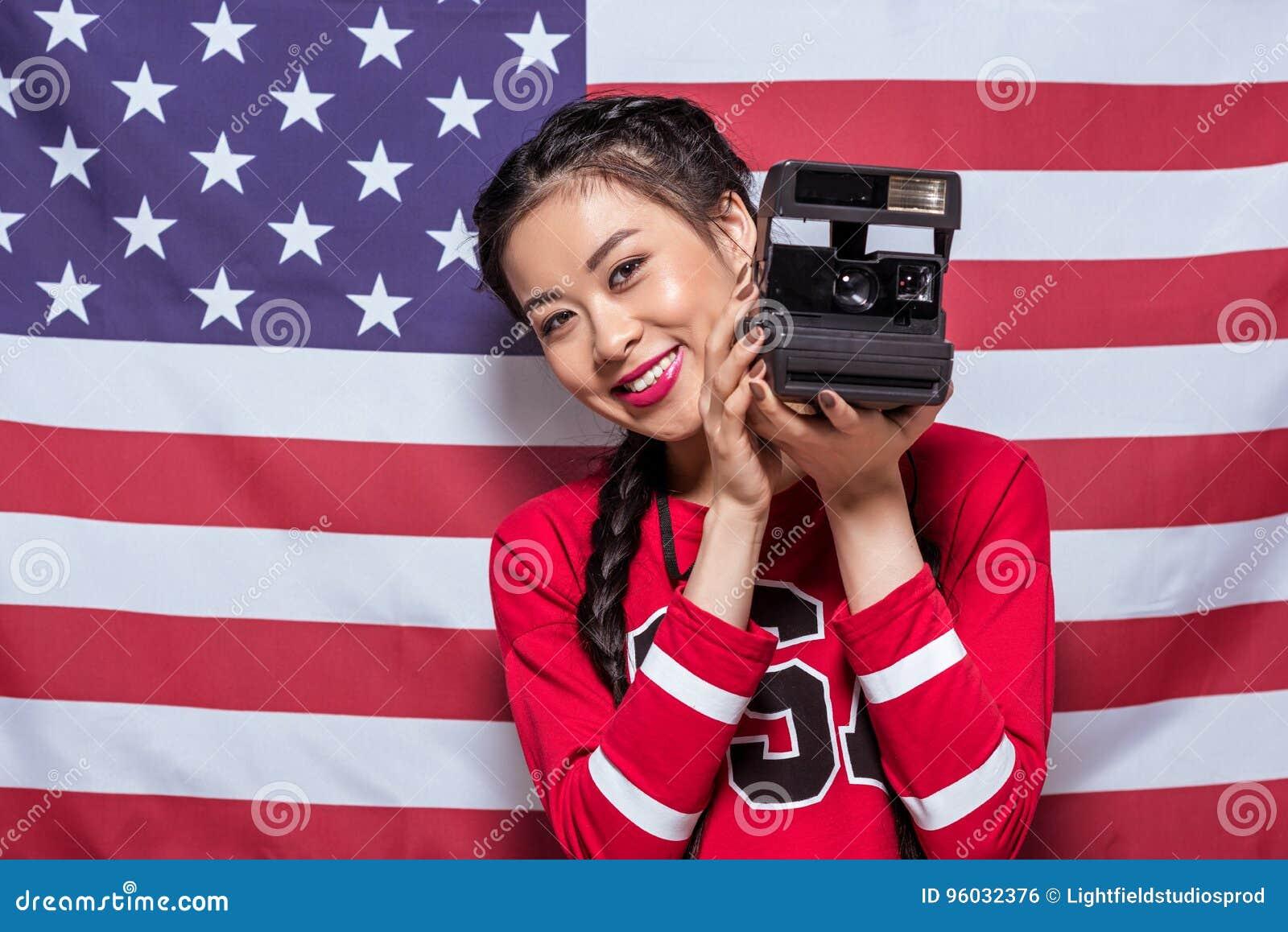Azjatycka kobieta trzyma retro fotografii kamerę z flaga amerykańską behind