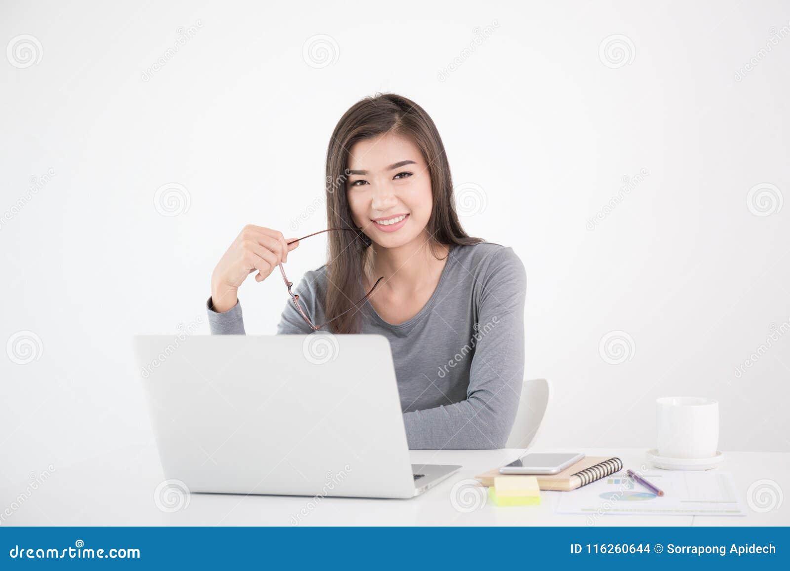 Azjatycka kobieta trzyma szkła w ręce i używa laptop, Żeński smil