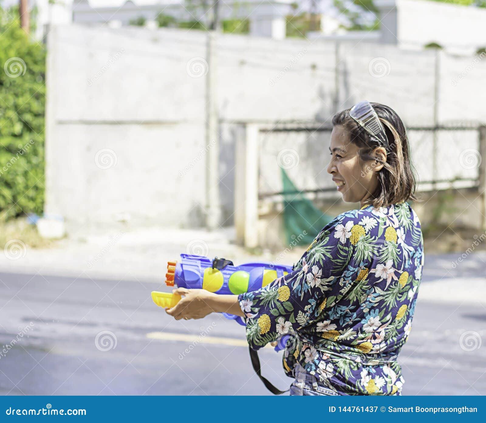 Azjatycka kobieta trzyma wodnego pistoletu sztuki Songkran festiwal Tajlandzkiego nowego roku w Tajlandia lub