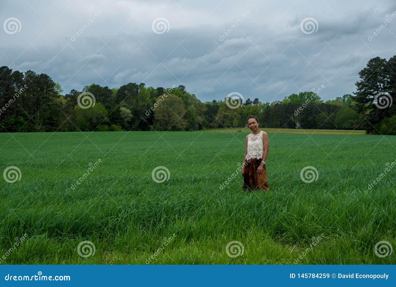Azjatycka kobieta w polu otaczaj?cym traw?