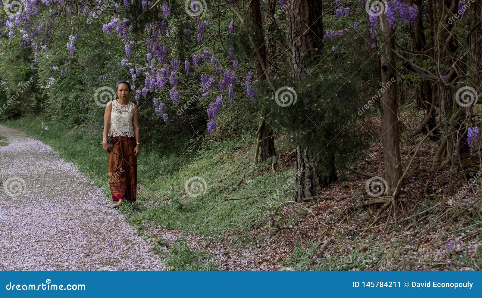 Azjatycka kobieta w sarongu odprowadzeniu na chodniczku zakrywaj?cym z ?a?o?? p?atkami