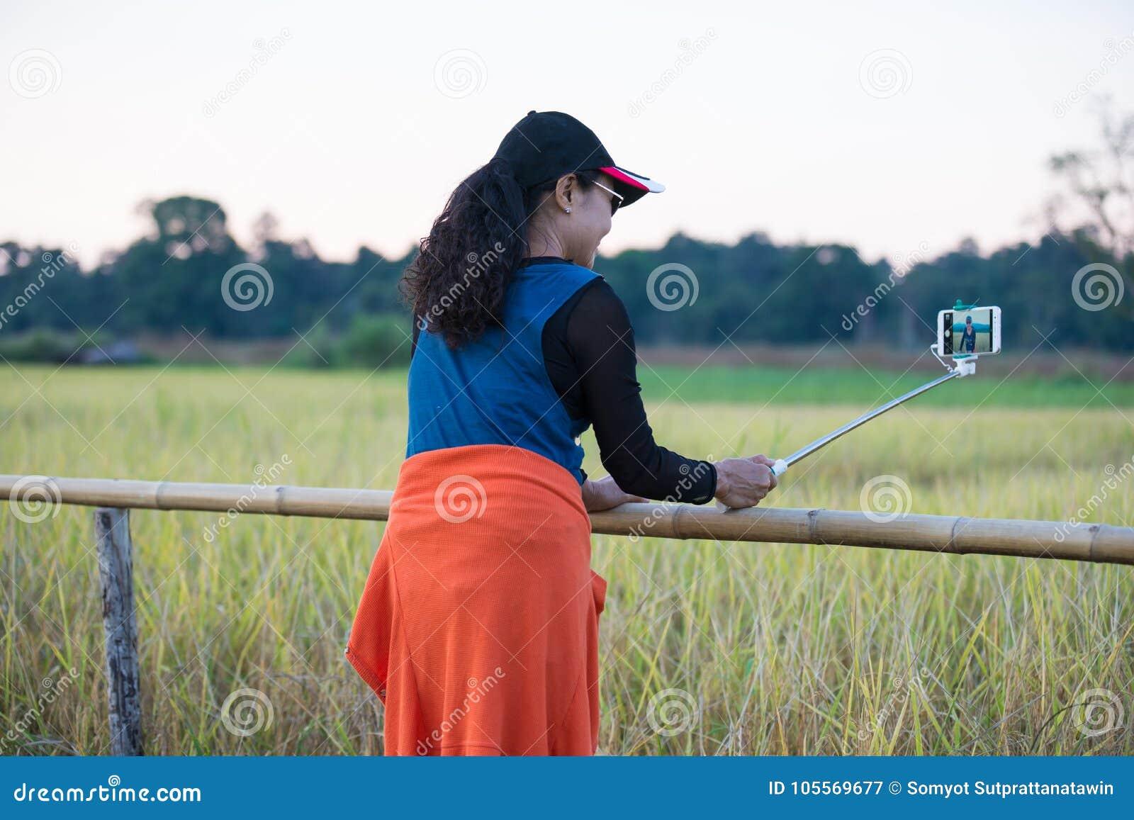 Azjatycka kobiety fotografia herself z selfie kijem